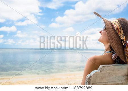 woman tourist relaxing in deck chair at beach in vacation