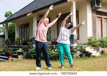 Active senior couple exercising with raised arms for warming up outdoors in the yard