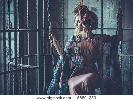 Luxurious  fashion stylish girl  in cage. Flower dress and a wr
