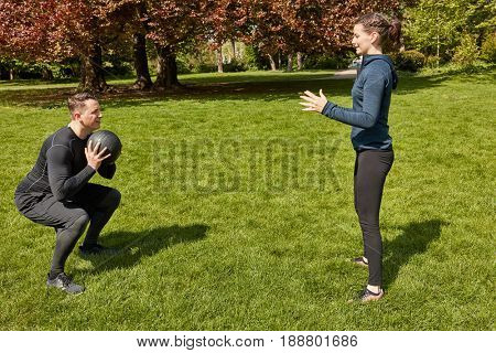 Man throwing fitness ball to Personal Trainer at the park in summer