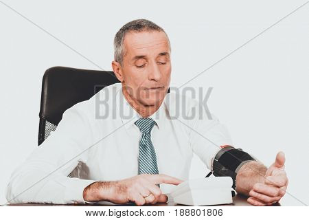 Mature businessman measuring blood pressure