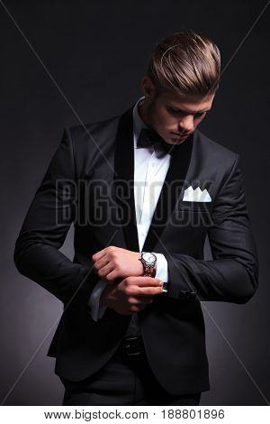 elegant young fashion man in tuxedo fixing his cufflinks while looking at them.on black background