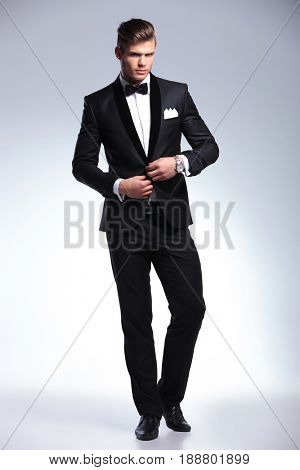 full length view of an elegant young fashion man in tuxedo unbuttoning his jacket while looking at the camera. on gray background