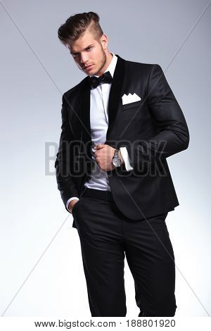 elegant young fashion man in tuxedo looking away while holding a hand in his pocket and one on his opened jacket. on gray background
