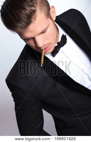 high angle view of an elegant young fashion man in tuxedo with a cigar in his mouth looking away from the camera. on gray background