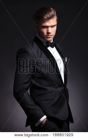 elegant young fashion man in tuxedo looking at the camera with a frightening expression while holding a hand in his pocket. on black background