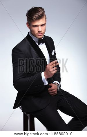 seated elegant young fashion man in tuxedo holding a cigar in his hand while looking at the camera. on gray background