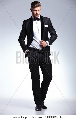full length picture of an elegant young fashion man in tuxedo holding a hand in his pocket and one on his jacket, looking at the camera with a serious expression .on gray background