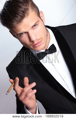 closeup of an elegant young fashion man in tuxedo holding a cigar between his fingers while looking at the camera. on gray background