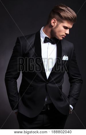 elegant young fashion man in tuxedo with his hands in his pockets looking away from the camera, down to his side.on black background