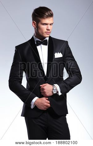 elegant young fashion man adjusting tuxedo with both hands while looking at the camera. on gray background