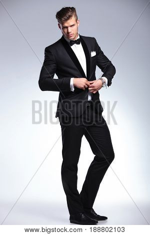 full length picture of an elegant young fashion man buttoning his tuxedo jacket while looking at the camera. on gray background