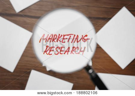 Paper note with text MARKETING RESEARCH through magnifier, closeup