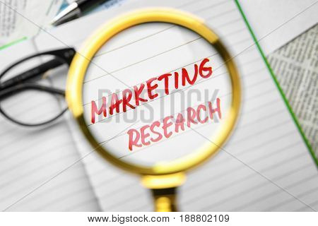 Open notebook with text MARKETING RESEARCH through magnifier, closeup