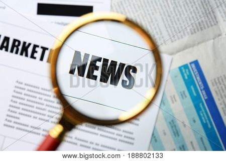 Paper sheet with word NEWS through magnifier, closeup. Marketing concept