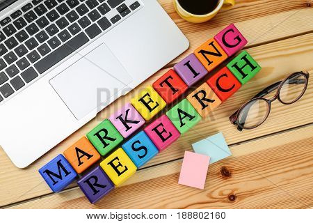 Colorful cubes with text MARKETING RESEARCH and laptop on wooden table
