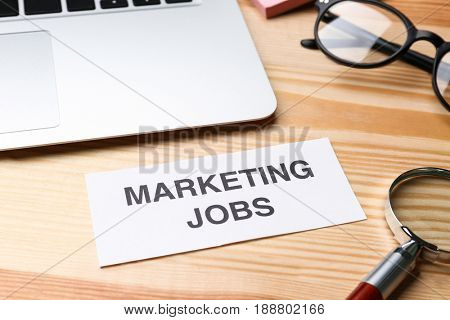 Paper sheet with text MARKETING JOBS and laptop on table