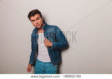 relaxed casual man holding his jacket by the collar while leaning on grey wall