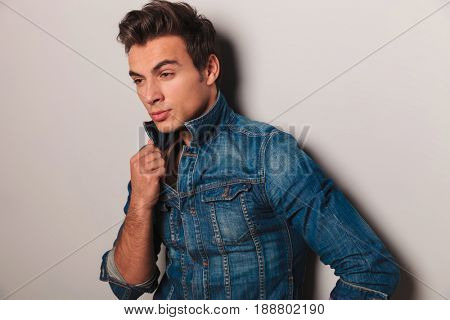 pensive young man leaning on wall and holds collar on grey background