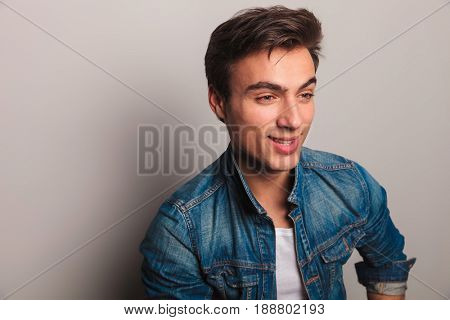 happy young man in jeans jacket looks to side and smiles on grey background