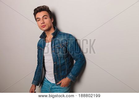 young casual man in jeans jacket leaning on grey wall