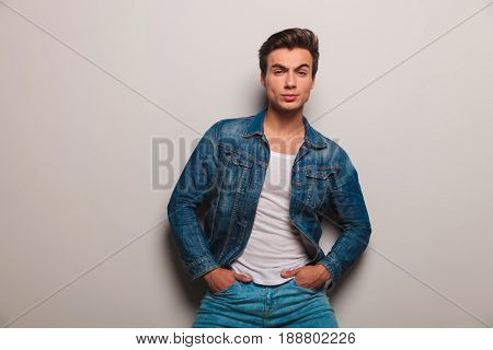serious man in jeans jacket standing with hands in pockets against grey studio wall