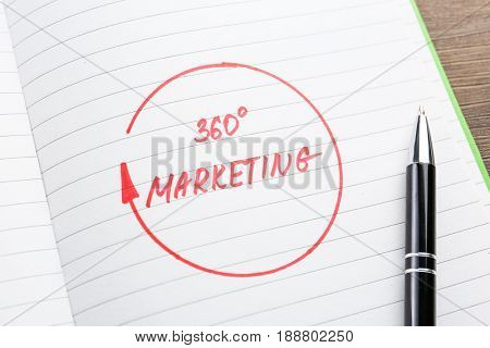 Open notebook with text 360 MARKETING, closeup