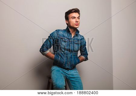 seated man in jeans jacket dreaming away on grey background