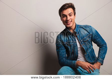 happy casual young man sitting on chair and smiles to the camera