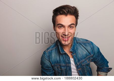 closeup portrait of a smiling young man in jeans jacket on grey background