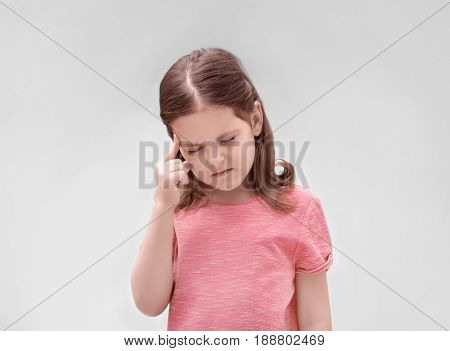Little girl suffering from headache on light background