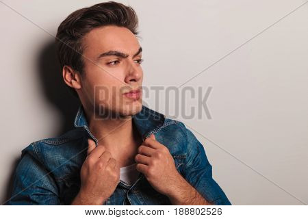 closeup portrait of young man holding jacket's collar and looks to side on grey background