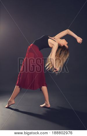 Beautiful young dancer on dark background