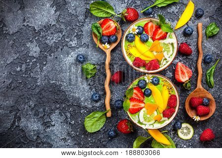 Green Smoothie in bowls for healthy breakfast. Fresh organic smoothie made from spinach, banana, spirulina,wheatgrass and lime with berries and fruits on black background.Top view, copy space