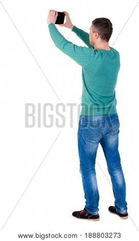Back view of man with tablet. Standing young guy. Rear view people collection.  backside view of person.  Isolated over white background. The man in black shoes photographed object in the sky.