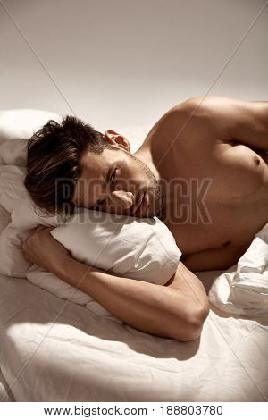 Handsome, fit man relaxing in bed