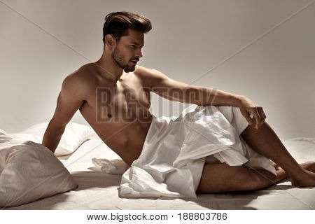 Handsome, muscular guy posing on the soft bed