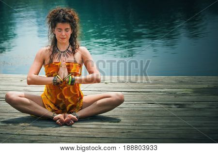 woman in a meditative yoga position sit on wooden pontoon on the lake wearing yellow  beach sarong and lot of bracelets and rings and necklace
