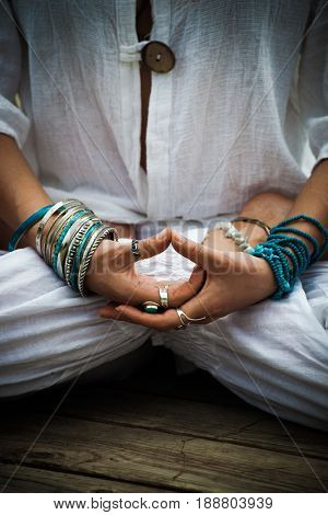 woman in a meditative yoga position outdoor  in white clothes wearing lot of bracelets and rings focus on hands in mudra