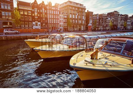 Amsterdam tourist boats in canal on sunset. Amsterdam, Netherlands