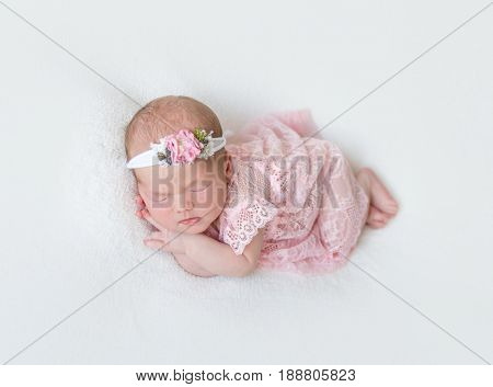 Cute infant with pink flowery hairband dressed in laced costume napping tightly on her side