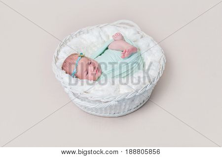 Adorable swaddled baby with legs moving, lying in kids basket, wearing headband