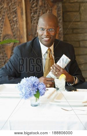 Black businessman holding newspaper in restaurant