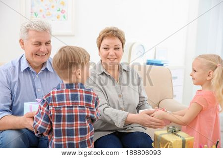Happy senior couple and their grandchildren exchanging gifts at home