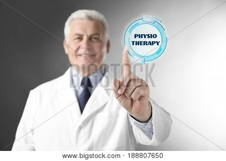 Rehabilitation concept. Doctor pointing on word PHYSIOTHERAPY against gray background