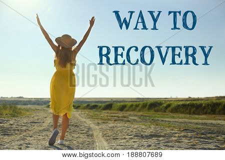 Rehabilitation concept. Woman walking on road. Text WAY TO RECOVERY on landscape background