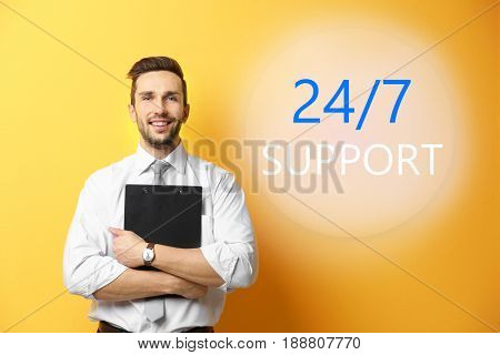 Help desk concept. Young man and text 24/7 SUPPORT on yellow background