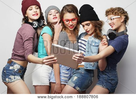 life style, tehnology and people concept: five hipster girls friends taking selfie with digital tablet