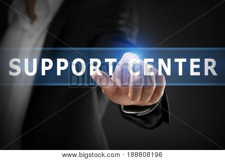 Help desk concept. Man pointing on text SUPPORT CENTER against black background, closeup