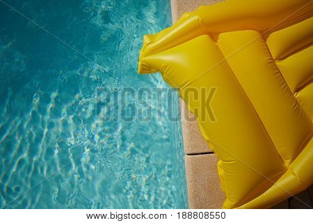 yellow air mattress  in a blue swimming pool.